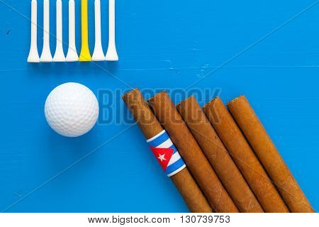Detail of luxury Cuban cigars and golf equipments on the blue wooden desk