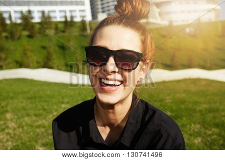 Portrait Of Beautiful Hipster Redhead Woman In Trendy Sunglasses And Bun Hairstyle, Sitting On The G