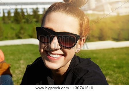 Close Up Shot Of Cheerful Student Girl In Black Shirt Having Rest In The Park After Passing Final Ex