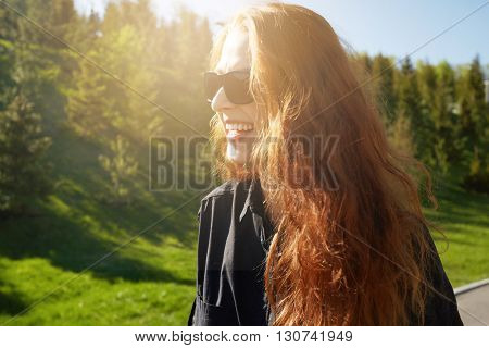Petty Smiling Woman With Long Red Hair Wearing Stylish Sunglasses, Having A Walk With Friends In The