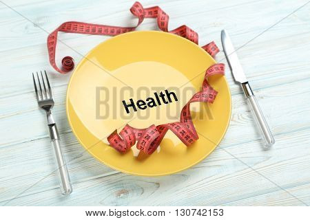Yellow plate on a blue wooden table, health