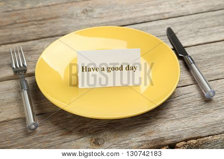 Yellow plate on a grey wooden table, have a good day