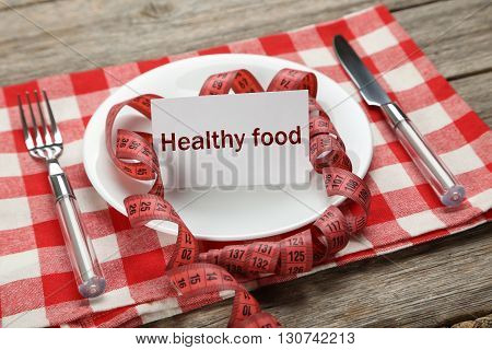 White plate on a grey wooden table, healthy food