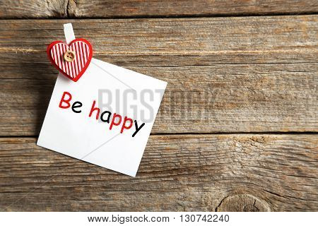 Blank paper hanging on rope on grey wooden background, be happy