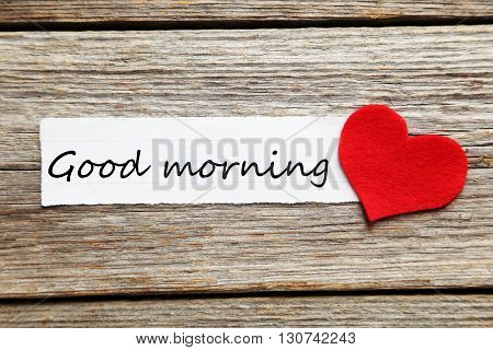 Red heart and sheet of blank paper on a grey wooden table, good morning
