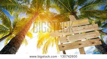 tropical destinations on sign and palm trees over beautiful sunny sky