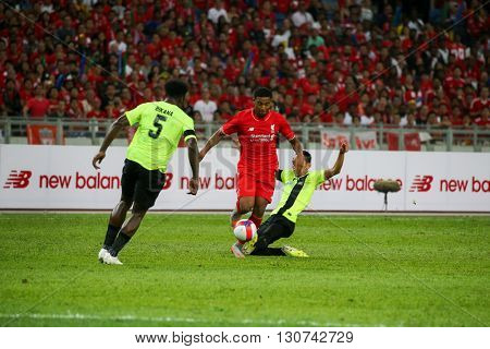 July 24, 2015- Shah Alam, Malaysia: Malaysia's Bikana (5) rushes for the ball against an attacking Liverpool player (red) in a friendly match. Liverpool Football Club from England is on an Asia tour.