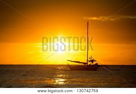 fishing boat silhouette in ocean over evening sunlight, beautiful seascape with dark clouds