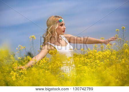 Beautiful young woman in field, enjoying in nature