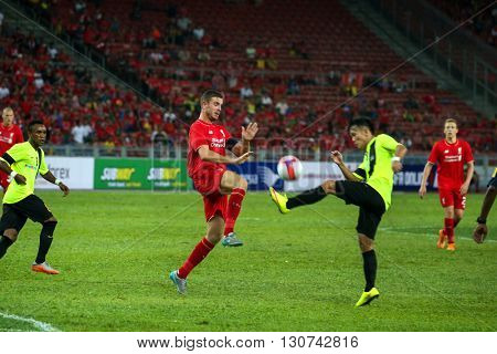 July 24, 2015- Shah Alam, Malaysia: Liverpool's Jordan Henderson (14) challenges a Malaysian defender to the ball in the friendly match. Liverpool Football Club from England is on an Asia tour.