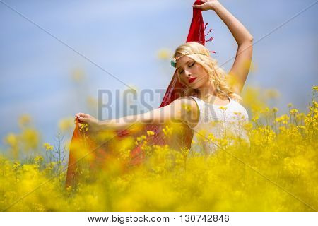 Portrait of beautiful young girl with red scarf in field