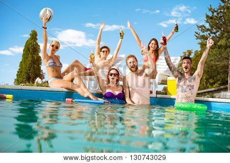 Cheerful young people in pool rejoice with beverage in raising hands in pool at summer