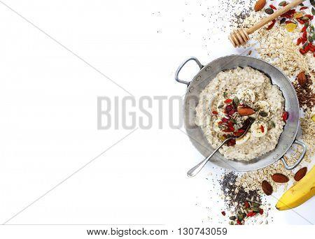 Healthy breakfast. Home made oatmeal porridge, goji berries, pumpkin and chia seeds  in a ceramic bowl on white background.