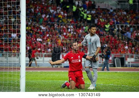 July 24, 2015- Shah Alam, Malaysia: Liverpool's Jordan Henderson (red) appeals to the referee in a friendly match against the Malaysian team. Liverpool Football Club from England is on an Asia tour.