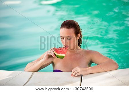 Portrait of young sexy woman with juicy piece of watermelon on swimming pool