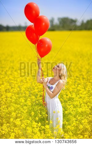 Young happy woman with balloons in a field of canola