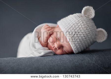 Newborn baby 2 weeks old sleeping on soft blue  fluffy blanket with funky woolen hat
