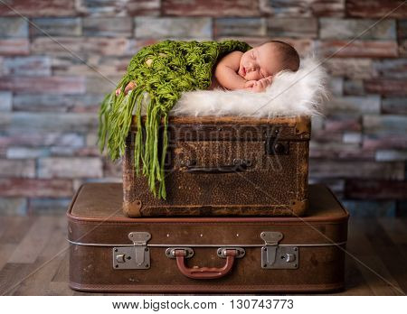 Little newborn baby peacefully sleeping on rustic  suitcases, travel or newborn photography concept
