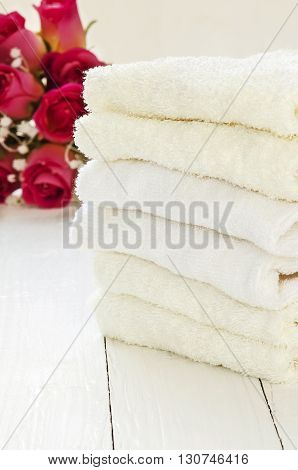 Stack of towels on white wooden background.