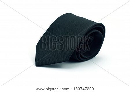 Roll of black tie on a white background. Necktie on white background.