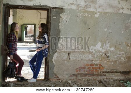 Teen girls standing in the aisle in an abandoned building.