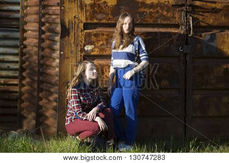Two beautiful teenage girls on the background of an old barn in the woods.