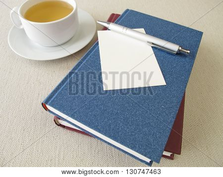 Books, blank sheet of paper and cup of tea