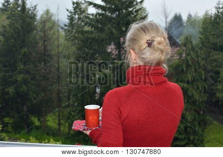 Woman relaxing drinking tea or coffee and watching lush conifer trees