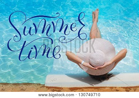 legs and a hat of woman in the pool water and words summer time.