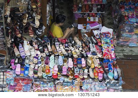 Hanoi, Vietnam - May 21, 2016: Vietnamese woman selling shoes, sandals and other merchandise product on whole sale at a street near Dong Xuan market, center of Hanoi capital.