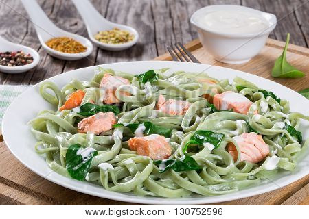 Salmon and Spinach Fettuccine pasta on white dish and table napkin cream sauce in a gravy boat spices in porcelain sauce spoon on wooden table Italian style studio lights top view