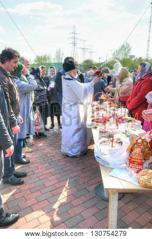 MOSCOW RUSSIA - May 01.2016: Priest blesses Easter cakes and eggs on the eve of the Easter holiday