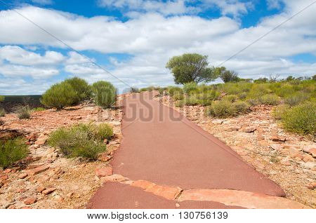Native flora and sandstone along the walking path in Kalbarri National Park under a blue sky with clouds in Western Australia.