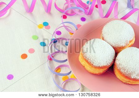 three doughnuts on pink plate over table with confetti and streamers