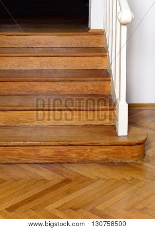 old wooden staircase with handrail and parquet floor