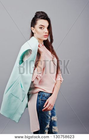 Portrait Of Young Brunette Girl Wearing In Pink Blouse, Turquoise Jacket, Ripped Jeans. Fashion Stud