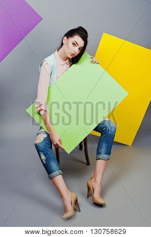 Full Length Of Beautiful Girl Sitting, Holding Green Blank Advertising Board , Over Gray Background
