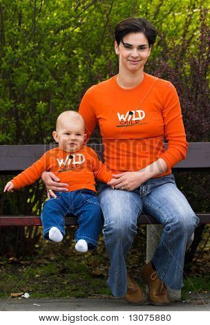 Baby and mother are having fun togather in the citypark on a sunny spring afternoon. They are wearing a similar orange T-shirt.