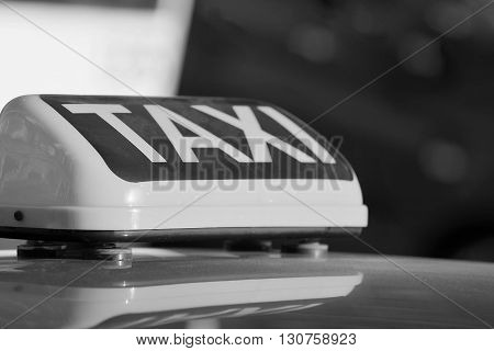 the big monochrome sign or symbol with a taxi inscription a closeup is located on a roof of the car and a blank space