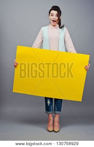 Young Girl With Surprised Face Hold Yellow Blank Paper. Young Smiling Woman Show Blank Card. Girl Wi
