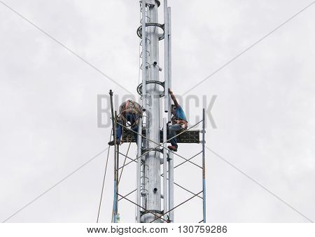 SELANGOR MALAYSIA - MAY 21 2016: Riggers are working at top of the monopole for installing scaffolding before radio frequency antenna and microwave dish installation.