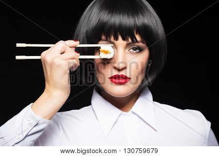 Sexy woman in wig holding sushi in front of eye