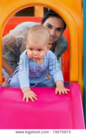 Baby and his mother are playing together on a playground.