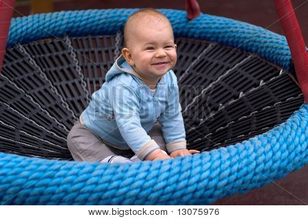 A baby is playing on a playground, he is sitting in a baby-swing.