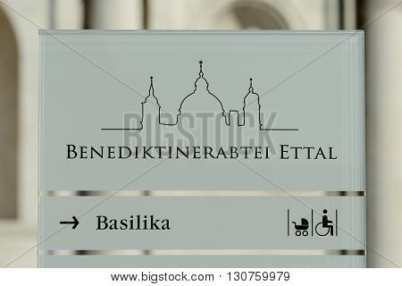 ETTAL, GERMANY - EBRUARY 12, 2016: Glass direction sign at Ettal Abbey a Benedictine monastery in the village of Ettal in Bavaria Germany.