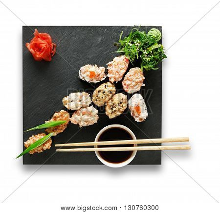 Japanese food restaurant, sushi gunkan plate or platter set. Set with chopsticks, ginger, soy sauce and wasabi. Sushi at black stone isolated at white background. Top view, Flat lay.