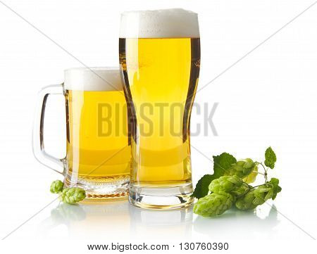Mugs Of Beer On Table With Hop Cones Isolated On White