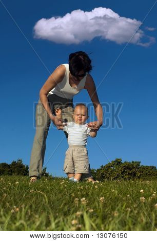 1 year old baby is practicing how to walk while his mother gives him a helping hand.