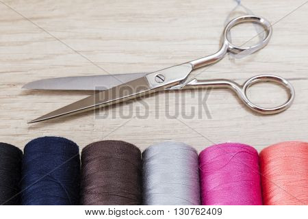 Several spools of thread of different colors and sizes with scissors