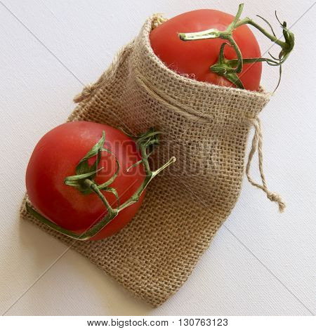 Two red vine tomatoes with a hessian bag.